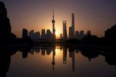 The sun rises behind the skyline of Shanghai and the Lujiazui financial district.