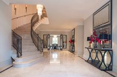 The grand entrance area ... features a sweeping staircase with bespoke balustrading and beautiful Jerusalem Crema Grey marble flooring with Marron Dior black marble border.