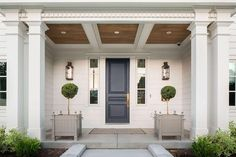 Chic home with portico filled with a plank ceiling over a dark blue front door accented with sidelights as well as gray planters filled with topiaries.