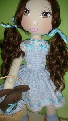 Boneca Dorothy e seu cachorrinho Totó <br>Mede 60 cm de altura, pesa 800 GR...é articulável, fica em pé sem suporte e pode sentar tbm. <br>Seu corpo é feito em algodão cru e revestido com manta acrílica, seu rosto é pintado a mão, cabelo dela é sintético de cor chocolate, o vestido é feito em tricoline azul chadrezinho, calça em tricoline branca, um par de sapato feito em tecido. Um par de meias azul claro, uma cestinha, um cachorrinho em feltro marrom, e a cobertinha do Totó também é em…