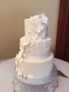 Small three tier round buttercream wedding cake with pearl detail and handmade sugar flower cascade