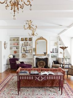 Eclectic living space with gold chandeliers, a fireplace, and a gold mirror