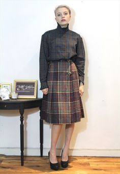 £30.00...70's vintage Grey red checked tartan kilt wool midi skirt/   This is a gorgeous hand picked vintage item by Pretty Disturbia, perfect to wear day or night. It can easily be dressed up or down!  FABRIC: 45% acrylic 20% polyester 15% wool   DETAIL: well made and fab deisgn -has a button fastening as well as a small buckle and beautiful check-very on trend!   STYLING- Our PD stylists would wear this unique kilt with a crop top and heels for a classic evening look or styled with a denim…
