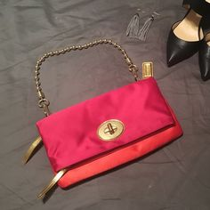 Coach Color Block Satin Clutch Great clutch by Coach!  Orange, pink and gold color palette. Fold over style, has a zipper at the top and in the inside part of the fold. Change compartment on the back, chain strap is detachable. There is one tiny spot on the inside of the fold, other than that item is in perfect condition! Always willing to take reasonable offers. Comes from a smoke free home. Coach Bags Clutches & Wristlets