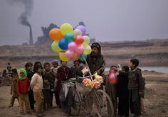 Pakistan: daily life - The Big Picture - Boston.com  Pakistani children gather by a vendor on a bicycle selling balloons on the outskirts of Islamabad. (Muhammed Muheisen/Associated Press) #