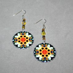 Silver dangle earrings with a sunflower mandala sacred geometry charm titled Perpetual Hope <br /> <br />These lightweight, dainty silver earrings begin with a dangle of chocolate and yellow Czech glass beads and citrine Swarovski crystals that accentuate the colors in the mandala charm that has scalloped edges that catch the light. The mandala charm is 1 –%2...