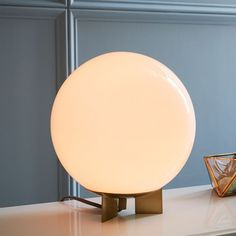 Round out your nightstand or side table with our Globe Table Lamp. Sitting on a three-point metal base, its gleaming glass orb casts a soft, diffused light