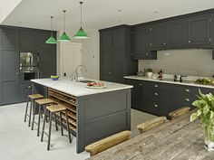 Dark grey/black kitchen design in battersea. Modern shaker style cabinets with burnished brass handles. Kitchen island with integrated wine rack and oak interior. With Calacatta composite marble effect worktops and grey porcelain floor tiles.