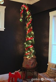 How to Make a Nine-Foot Grinch Tree - 5′ potted cedar hedge (you can certainly purchase a larger hedge, perhaps 8′ tall, which would make this project even easier!) 2-3 x 4′ long, green, plant stakes Cedar boughs (extra cedar branches usually sold for wreath-making or swags) Green garden wire Large pot tray to fit the nursery pot Burlap sack Ribbon to tie sack Miniature tree lights 5 yards of 6″ decor mesh 1 large Christmas ornament Many smaller ornaments (like these clay acorns)
