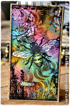 Beautiful background of black rubber stamped images, create a mask to block off areas of the stamped image you want to keep white, sponge background with multiple colors applied from ink pads, then stencil patterns with darker ink pad. Layering Art Journey stamps nature journal cover bee.