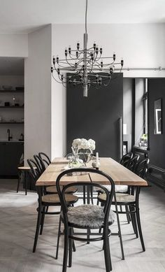 Scandinavian dining and living room, with interior in black with wooden details.