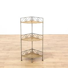This corner shelf is featured in a woven wicker and wrought iron. This cottage chic style display shelf has 3 woven tiers, decorative scroll details, and rounded edges. Darling piece that's perfect for storing spices and cooking oils! #cottagechic #storage #bookcase&shelving #sandiegovintage #vintagefurniture