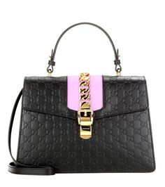 Gucci - Signature Sylvie embossed leather shoulder bag - Opt for an iconic silhouette with Gucci's Signature Sylvie shoulder bag. Crafted in Italy, this piece features black leather embossed with the designer's signature GG logo. Lilac-hued panelling and gold-tone hardware give this covetable recognition appeal. Lined with soft suede, there's enough room inside for all your day-to-day essentials. seen @ www.mytheresa.com