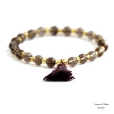 Taupe lotus - Is made of smoky quartz, golden glass beads a taupe colored tassel and an elastic string. Wild animals. Unexplored thicket. Tropical heat. Unknown noises. Colorful flora. Exotic fruits. Welcome to the jungle!  Six men's bracelets and a necklace are inspired by the tropical jungle vibe.