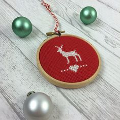 A handmade cross stitch Christmas ornament framed in wood.  This mini sampler is perfect for bringing a little touch of Christmas to your
