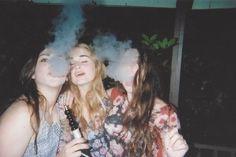 three girls smoking .