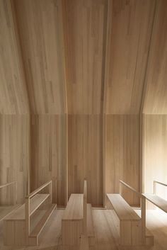 The internal walls, floors and ceiling are all covered in the same light wood, which provides a dramatic roof above the minimal church pews, which are also made from pale timber.