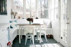 A quaint breakfast nook opens onto a screened porch blending exterior and interior.