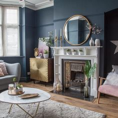 Living room makeover with dark blue walls, pink sofa and gold accessories