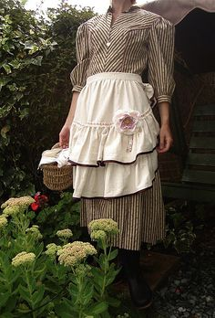 Apron with two layers, loose ruffles, lightweight fabrics.  And of COURSE a corsage.
