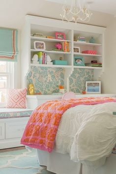 Sweet girl's room with built-in window seat and desk with hutch featuring a Thomas Paul Aviary Robin Fabric memo board with matching window seat cushion topped with a geometric coral pink pillow below a sunny window dressed in an aqua blue roman shade with coral grosgrain trim. The bed is dressed in pretty white bedding layered with a pink and orange dotted coverlet over hardwood floors layered with an aqua blue and white moroccan rug.