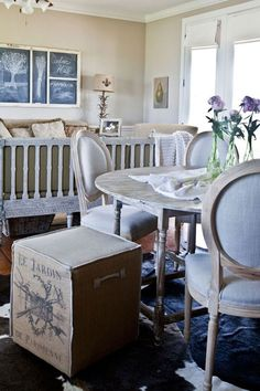 She chose Swedish Gustavian reproductions that convey a rustic elegance, like a hand-carved bench with a slatted back and a round dining table, and mixed in some country chic items, like a burlap-upholstered Aiden Gray Home ottoman with French wording and a table lamp with fleur-de-lis accents. Durable animal-skin rugs protect the wide-planked wood floors.