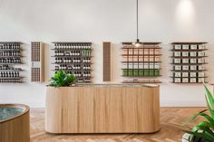 Custom furniture - reception desk - aesop store - wooden finish - rounded corners - plants