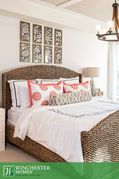 a wicker bed frame and wood chandelier make the master bedroom of the hadden model naturally