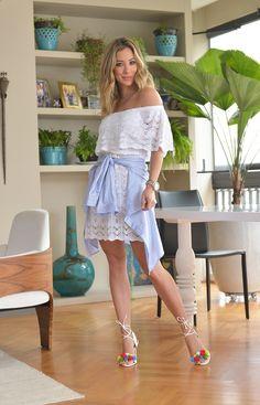 Look do dia Helena Lunardelli: vestido branco de tricô branco com camisa listradinha amarrada e sandália de pom poms coloridos.