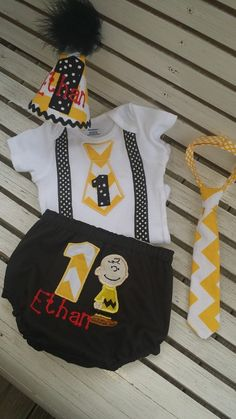 Charlie Brown themed birthday cake smash outfit comes with applique onesie with ribbon suspenders , themed fully lined diaper cover, party hat with childs age and name apone request and a chevron lttle man tie. All pro sewn from quality fabrics . custom sizes . colors and themes available just me...