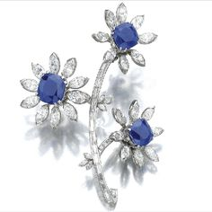 Sapphire  & Diamond Brooch - Designed as a stylised floral spray, the flower head centres, mounted en tremblant, set with three cushion-shaped sapphires weighing 6.71, 7.00 and 10.21 carats respectively, the petals set with marquise-shaped diamonds, the stem with baguette diamonds.