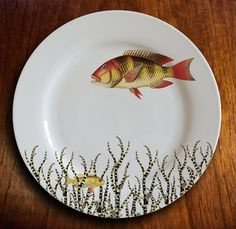This 10.25 inch dinner plate features a fiery-hued fish, bold in color and style. Below her is a small yellow fellow, cached amongst a black