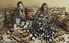 two DVF models, both wearing bold DVF monochrome polka-dotted ensembles, recline on an equally eye-catching tiger print sofa at the designer's home