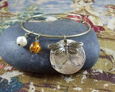 Dragonfly and Amber Charm Bangle Bracelet with antique white baroque pearl #Outlander https://www.etsy.com/listing/224314871/dragonfly-and-amber-charm-bangle…