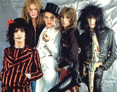 New York Dolls | he New York Dolls are an American hard rock band formed in New York City in 1971. Along with the Velvet Underground and the Stooges, they were one of the first bands in the early punk rock scene. The line-up at this time comprised vocalist David Johansen, guitarist Johnny Thunders, bassist Arthur Kane, guitarist and pianist Sylvain Sylvain, and drummer Jerry Nolan; the latter two had replaced Rick Rivets and Billy Murcia, respectively, in 1972.