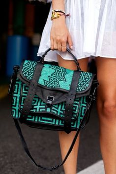 turquoise messenger style bag with tribal/geometric designs.