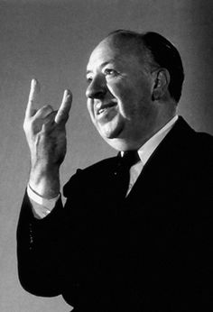 Alfred Hitchcock doing the either 'sign of the horns' gesture or 'I love you' in sign language, 1960s