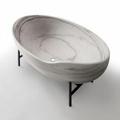 the suspended ellipsoidal marble bathtub evokes the ancient tibetan bells.