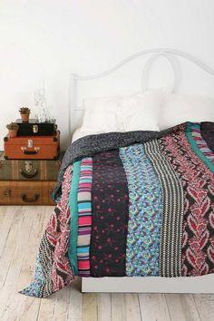 chambre bohème blanche avec une couverture patchwork originale et table de chevet improvisée en valises entassées