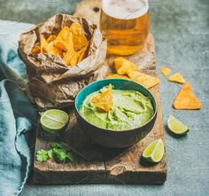 #Guacamole sauce & mexican corn chips  Fresh guacamole sauce in blue ceramic bowl mexican corn chips glass of wheat beer on rustic wooden serving board over grey concrete table background selective focus