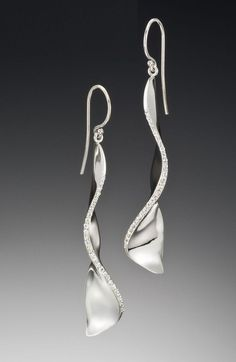 A modern earring design by Adam Neeley. Covet diamond earrings are curvaceous and enchanting. This unique earring design features diamonds sparkling from undulating white gold forms. Also available in rose gold or yellow gold.