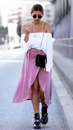 Street style look blusa ombro a ombro, saia rosa e botas.