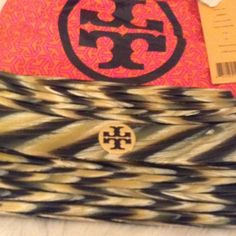 Tory Burch Faux Horn Clutch Black-multi colored small resin clutch. Colors zig-zag together and include black, yellow, green and white (roughly). Small logo on outside as well as inside. Bag is in very mint condition. It does fold in a bit I guess just due to not being used and sitting over time. Comes with Tory Burch dust cover. Tory Burch Bags Clutches & Wristlets
