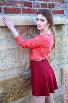 Beauty in red skirt by the wall