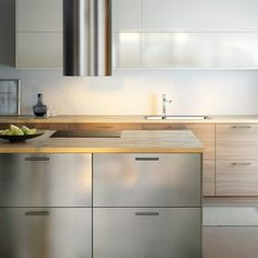Modern IKEA kitchen with wooden worktops and a combination of stainless steel, light-wood and high gloss light cabinet doors