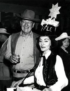 John Wayne holding a drink as he stands with his wife at a children's charity in Hollywood, June 1964.