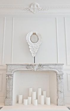 French living room features walls clad in decorative wall moldings and ornate beaded crown moldings lined with a French marble fireplace filled with candles. Candles In Fireplace, Fake Fireplace, Fireplace Wall, Fireplace Design, Fireplace Ideas, Fireplace Decorations, Concrete Fireplace, Natural Stone Fireplaces, Marble Fireplaces