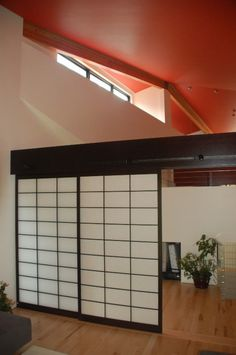 The Rail And Shoji Door System Is Attached To Black Beam That Divides Open E With High Ceiling