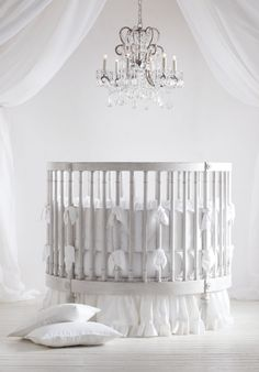 A stylish, circular crib hand-finished in weathered white tones for an heirloom feel.