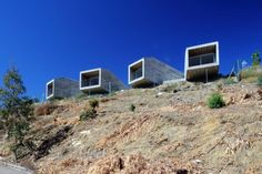 """Residential Architecture: 4 Bungalows by Estudio Arquitectura Hago: """"..a series of residences perched upon theedge of a hill..two independent structures each contain two dwellings which branch and split to producea total of four separate cantilevers. formed entirely from concrete, the volumes extend over the landscape and precisely framevistas of the orellana reservoir. accessible by one of the homes in each building, a central patio is generated for anoutdoor eating area.."""" Distinctive…"""